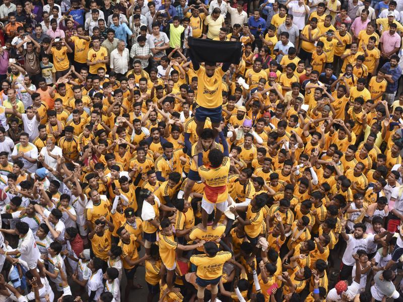 The Akhil Dahi Handi Pathak forming a human pyramid with another team while displaying a  black flag during the Gopal Kala celebrations at Dadar on Thursday. (kunal patil/ht)