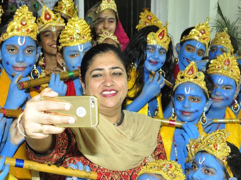 A teacher clicks herself with children dressed as Lord Krishna in Patiala. (Bharat Bhushan/HT Photo)