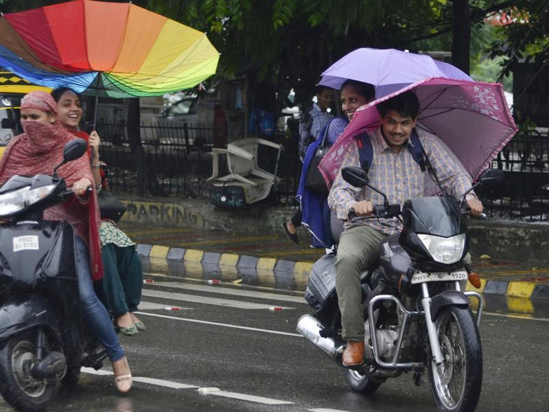 Commuters in the rain in Amritsar on Saturday.  (Sameer Sehgal/HT Photo)