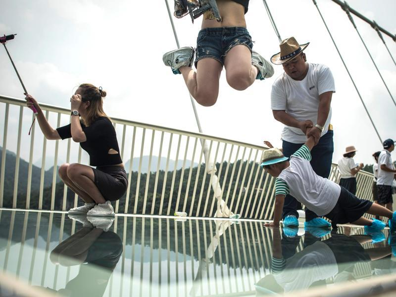 Some enjoy clicking pictures on the bridge, while some others enhance their experience by jumping with joy and thrill. It would really be so much fun to be suspended in air, while being on a glass bridge suspended, isn't it? (AFP)