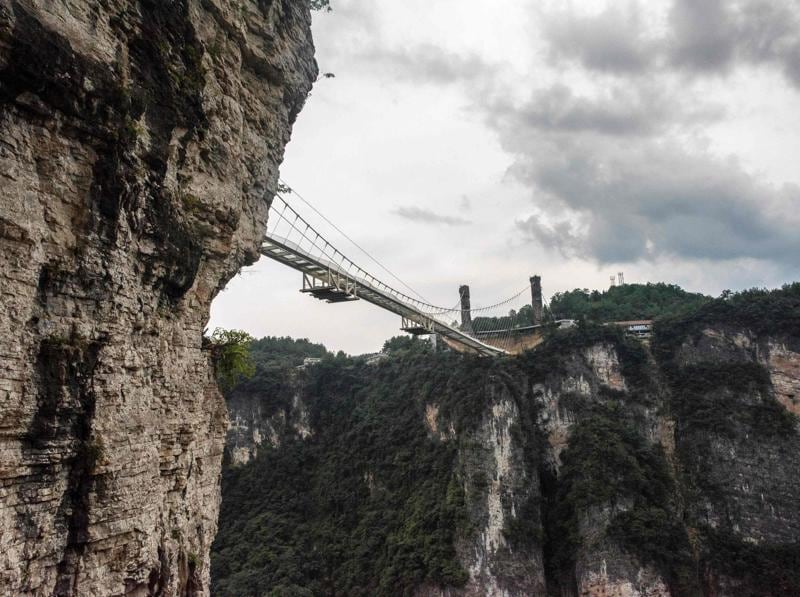 The bridge spans 430 metres (1,410 feet) and rises about 300 metres (984 feet) above a valley in a scenic zone, making it the world's highest and longest glass-bottomed bridge. (AFP)