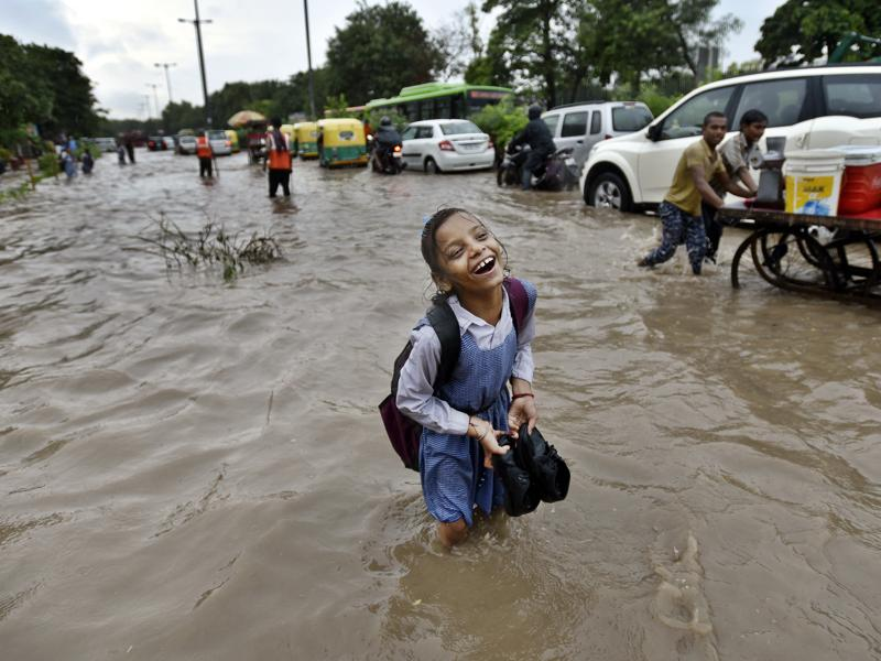 Heavy showers on Wednesday morning inundated vast swathes of the national capital region. Delhi received 65.7mm rainfall in the morning, leading to traffic jams and harassed commuters. A school girl sees the bright side of wading through a flooded road near Turkman Gate in New Delhi.  (Arun Sharma/HT PHOTO)