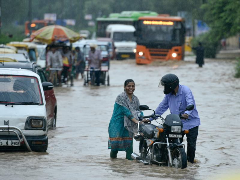 The downpour, coupled with strong winds and lightning for more than four hours in the morning, flooded roads across Delhi with hundreds of people stranded at bus stops and Metro stations.  A couple in Turkman Gate pushes their bike after being caught in the rain. (Arun Sharma/HT PHOTO)