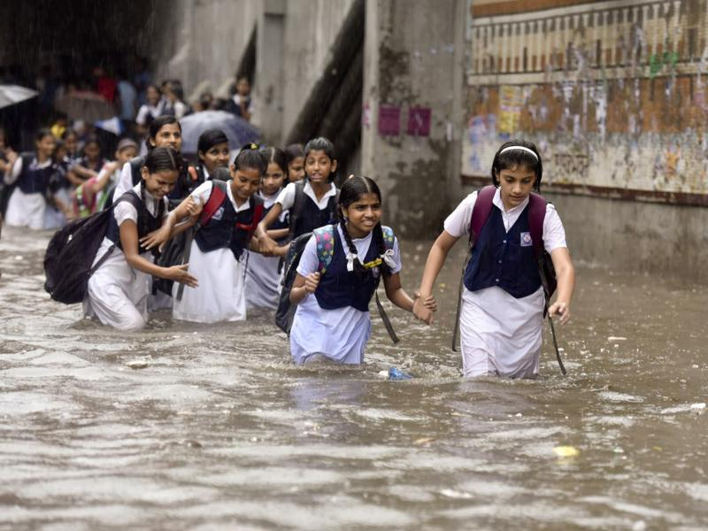 "The weather department says 53 mm of rain was recorded in Delhi-NCR in just two hours. The ""unusual"" amount of rains caught this group of school students off guard. (Raj K Raj/HT PHOTO)"