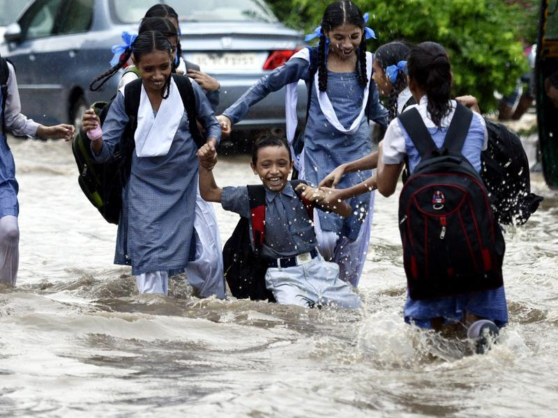 This group of school students made the most of walking through a flooded road in central Delhi. (Arun Sharma/HT PHOTO)