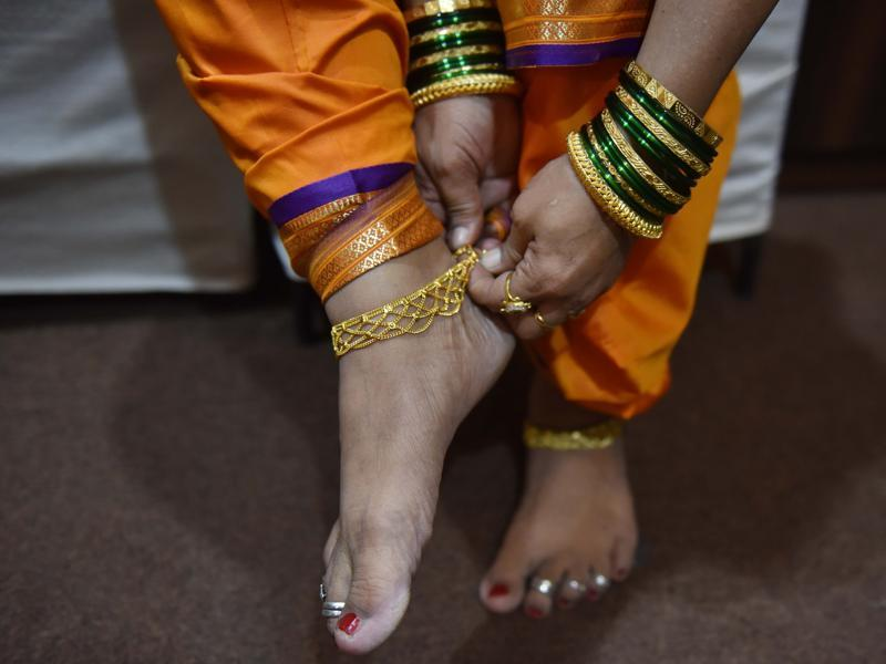 A woman wears an anklet before her performance. (Pratham Gokhale/HT PHOTO)