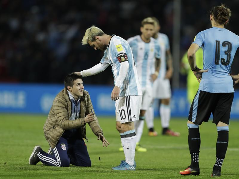 A fan who invaded the pitch kneels in front of Argentina's Lionel Messi. (AP Photo)