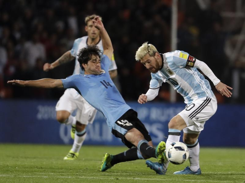 Argentina's Lionel Messi, right, fights for the ball with Uruguay's Nicolas Lodeiro. (AP Photo)