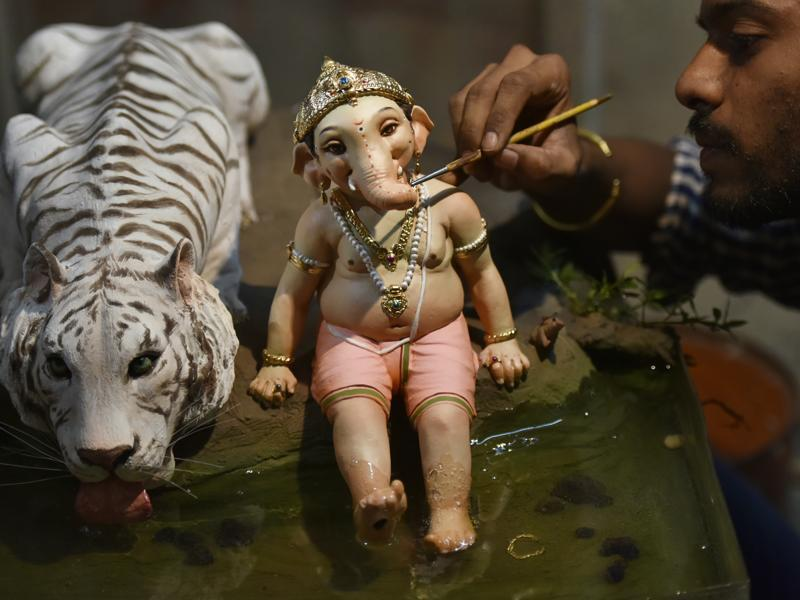 MIGHTY LORD: Artist Vinod Shinde gives finishing touches to an idol made of clay. (Anshuman Poyrekar/HT)