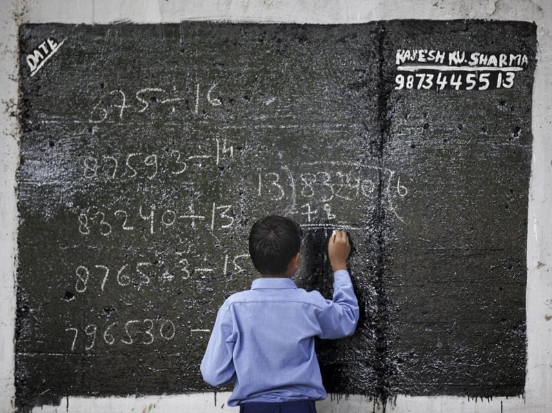 A student in Rajesh Gupta's class writes on a blackboard.  (Raj K Raj/HT PHOTO)
