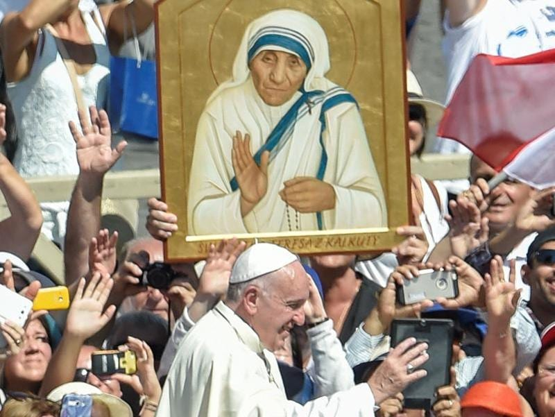 Pope Francis (C) waves to faithful as he leaves after a Holy Mass and canonisation of Mother Teresa of Kolkata, on Saint Peter's Square in the Vatican, on September 4, 2016. Mother Teresa, the nun whose work with the dying and destitute of Kolkata made her a global icon of Christian charity, was made a saint on September 4, 2016. Her elevation to Roman Catholicism's celestial pantheon came in a canonisation mass in St Peter's square in the Vatican that was presided over by Pope Francis in the presence of 100,000 pilgrims. / AFP PHOTO / ANDREAS SOLARO (AFP)