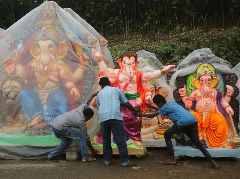 Vendors push an idol of Ganesha in Bangalore. Lord Ganesha's idols of all sizes and in different colours and 'avtars' were installed in decorated 'pandals' or on makeshift platforms in residential neighbourhoods and commercial centres. (Aijaz Rahi/AP)