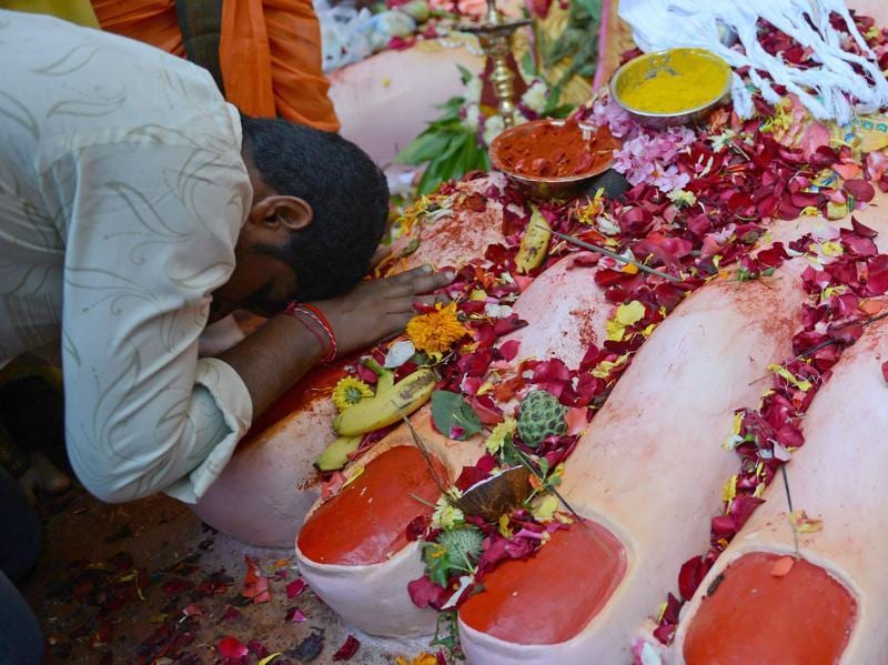 A devotee offer prayers at the foot of a 17- metre tall idol of Lord Ganesha in Hyderabad. Devotees bring home idols of Lord Ganesha in order to invoke his blessings for wisdom and prosperity, during the eleven-day long festival which culminates with the immersion of the idols in water bodies. (NOAH SEELAM/AFP)