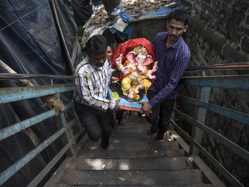 Devotees carry an idol on Ganesh Chaturthi at Chinchipokhli in Mumbai.  Around 40,000 more homes in Mumbai will host Ganpati this year, taking the tally of household idols to 2.25 lakh in the city. (Satish Bate/HT PHOTO)