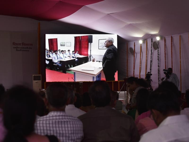 People watch on a digital screen as President Pranab Mukherjee teaches students of Class 12 of Dr Rajendra Prasad Sarvodaya Vidyalaya at President's Estate in New Delhi on Monday.  (Vipin Kumar/HT PHOTO)