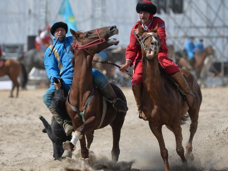 Kazakh and US (red) riders play the traditional Central Asian sport Buzkashi. (AFP Photo)