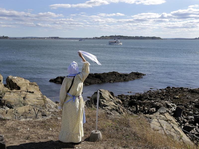 Sally Snowman waves to a cruise boat from Little Brewster Island in Boston Harbor.  (AP)