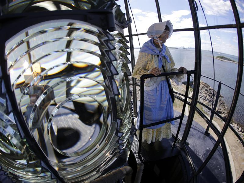 In this photo, Sally looks outside the lantern room while standing next to the Fresnel lens. (AP)