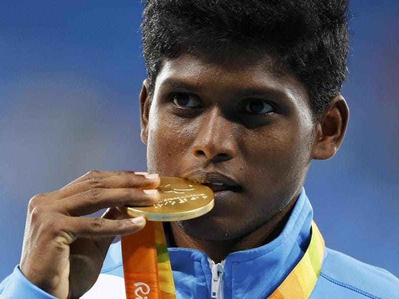 Mariyappan Thangavelu bites his gold medal as he poses for photographers on the podium. (REUTERS)