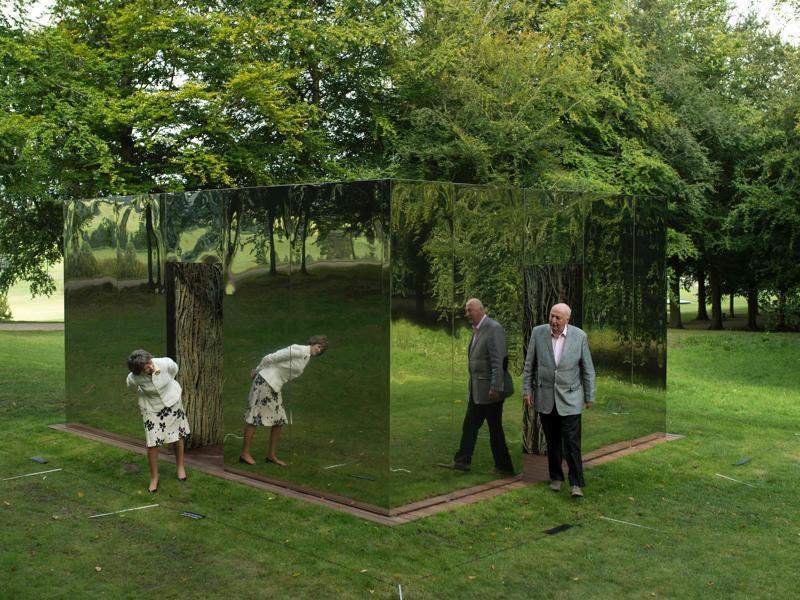 The Duke and the Duchess of Devonshire examine a sculpture by Spanish artist Cristina Iglesias, that features in the 'Beyond Limits' exhibition held near Bakewell, northern England, on Friday.   (AFP)