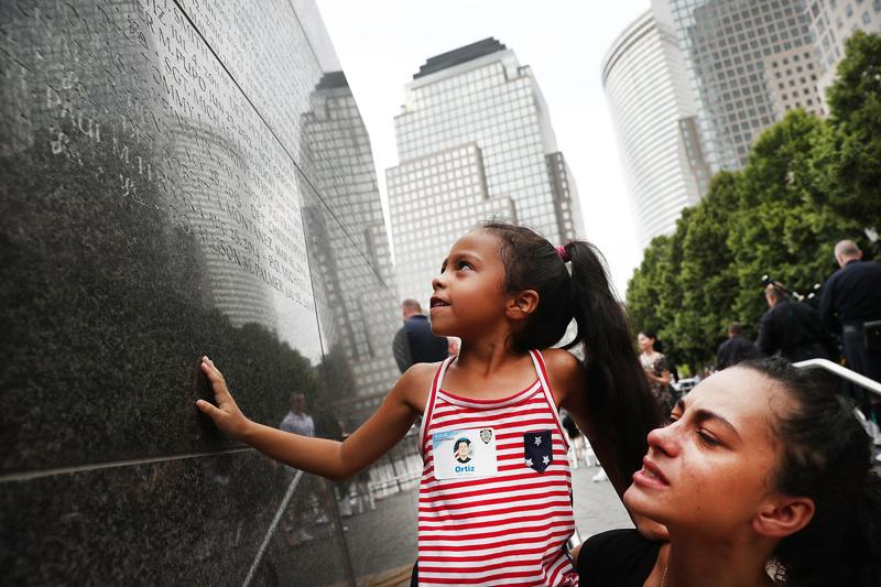 A woman holds up her daughter as she looks for her grandfather, New York city police officer Edwin Ortiz's name at a wall commemorating fallen officers, on September 9, 2016. Families gathered at the wall to mark the 15th anniversary of the 9/11 attacks and the officers who were killed during and after the event. Detective Ortiz died from illnesses he contracted from inhaling toxic materials during the rescue and recovery operations at Ground Zero.  (AFP)