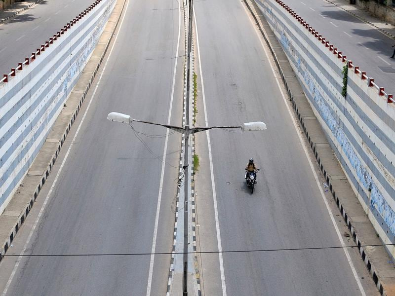 A motorist rides a bike on an empty road on the day of a statewide strike called by various organisations to protest against a Supreme Court order asking the southern state of Karnataka to release water from the river Cauvery to the neighbouring state of Tamil Nadu, in Bengaluru.  (Reuters Photo)