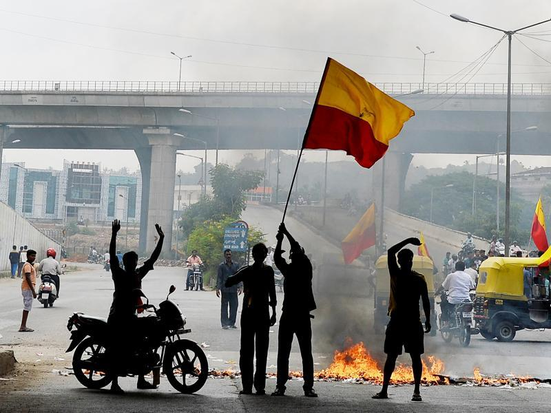 Activists wave the Karnataka flag as they block traffic on a connecting road during a statewide strike in Bengaluru. Karnataka is facing an acute shortage of water in its reservoirs, and rivers as the state has only received subpar rainfall in the catchment areas leading to protests by farmers and pro-Kannada organisations refusing to share water with its neighbouring state. / AFP PHOTO / MANJUNATH KIRAN (AFP Photo)