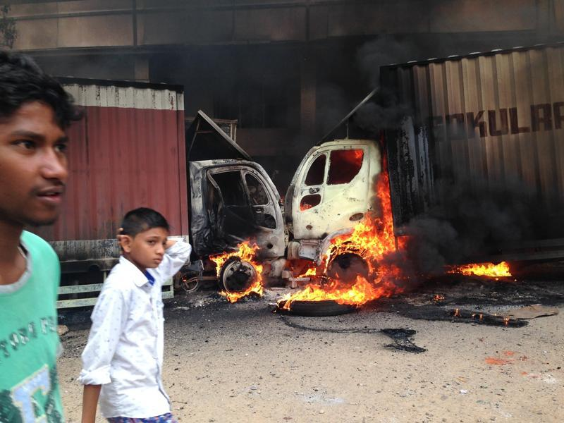 People walk past as two trucks that came from Tamil Nadu and were set ablaze by protesters in Bengaluru.  (AP Photo)