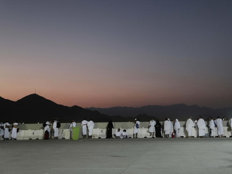 Pilgrims watch sunrise before they make their way to cast stones at a pillar on the first day of Eid al-Adha, in Mina, Saudi Arabia. (AP Photo)