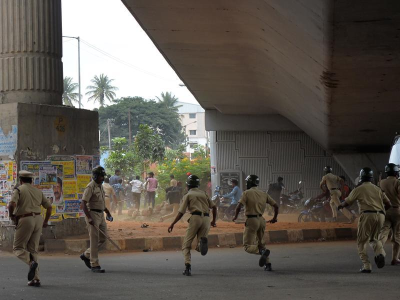 Police personnel chase agitated activists as the Cauvery water dispute erupted into violence following the Supreme Court's order to release water to Tamil Nadu, in Bengaluru. (AFP Photo)