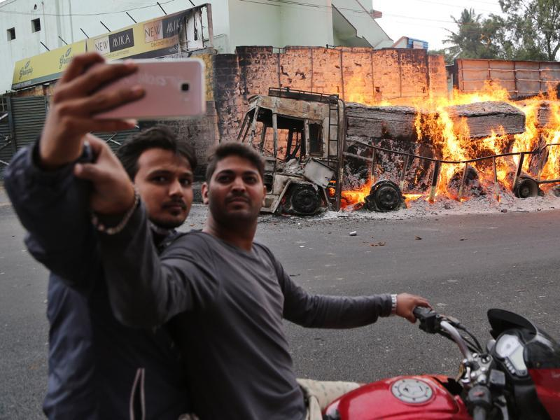 Two men on a motorcycle stop to take a selfie with a burning truck in the background. (AP Photo)