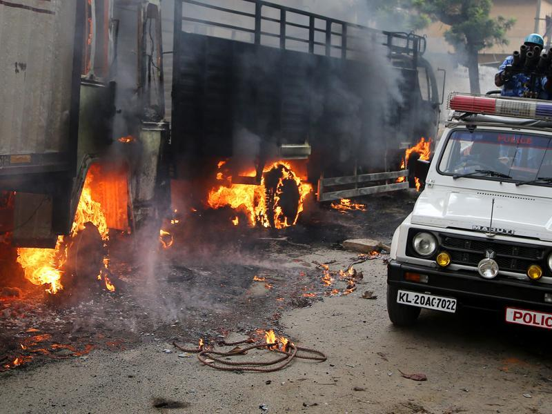 An armoured vehicle of riot police drives past burning trucks belonging to the neighbouring Tamil Nadu after they were set ablaze by angry mobs in Bengaluru. (AP Photo)