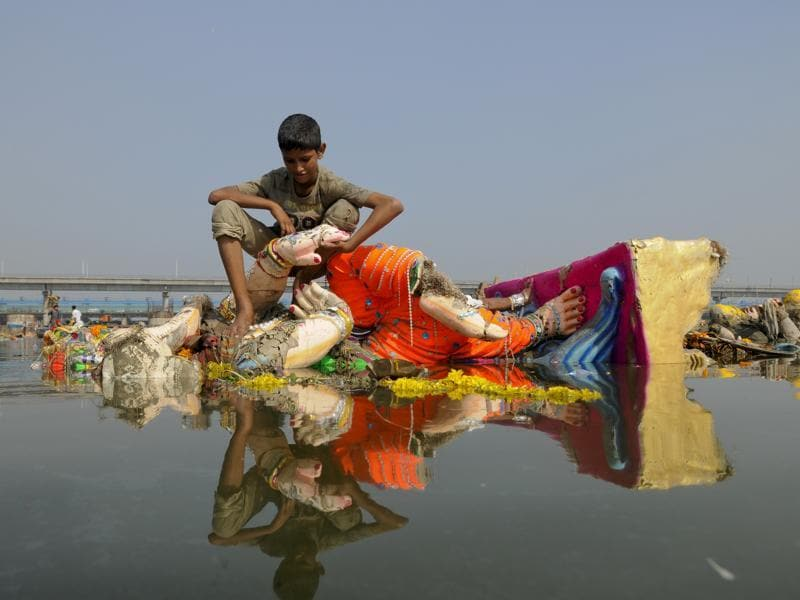 Perched on a barely submerged idol, a boy looks for scrap in the stationary waters. (Burhaan Kinu/HT PHOTO)