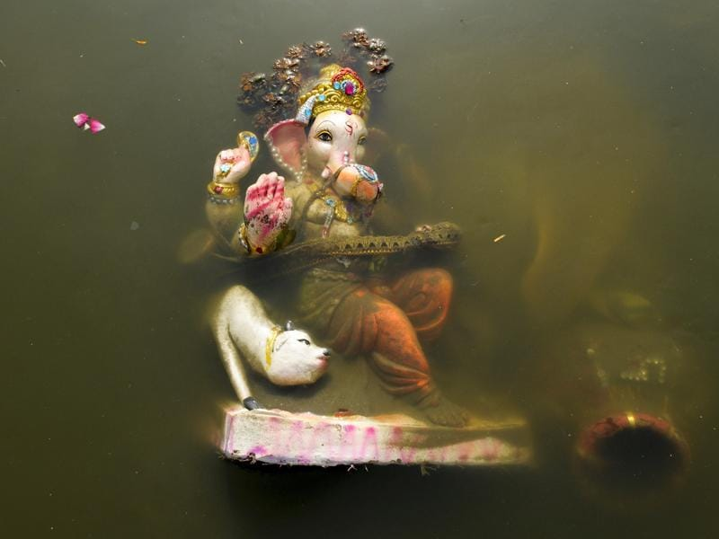 The barely thriving Yamuna does not have enough water for towering idols to be submerged in. (Burhaan Kinu/HT PHOTO)