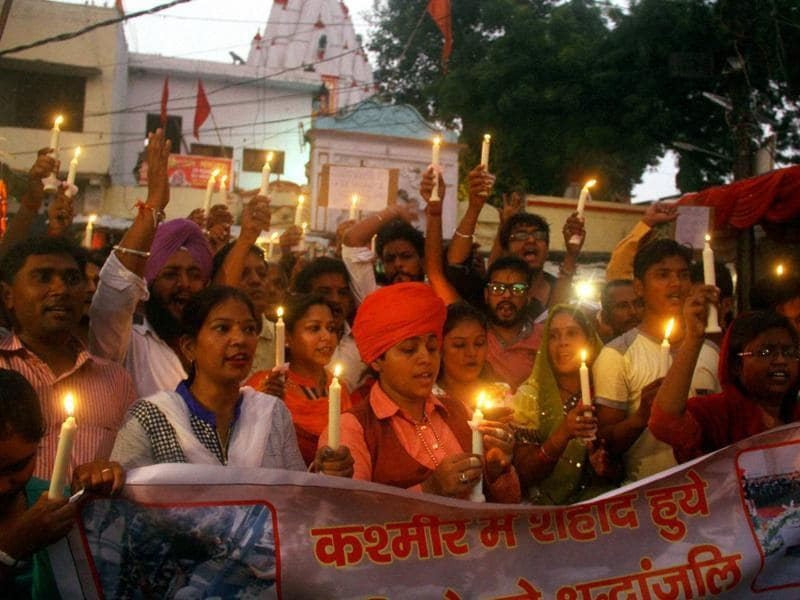 People take part in a candlelight vigil to pray for soldiers killed in the Uri attack. (PTI)