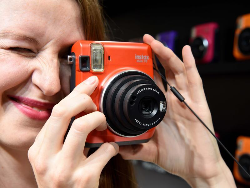 A happy visitor tries out the Fuji Instax polaroid camera at the Fuji stand.   (Patrik stollarz / AFP)