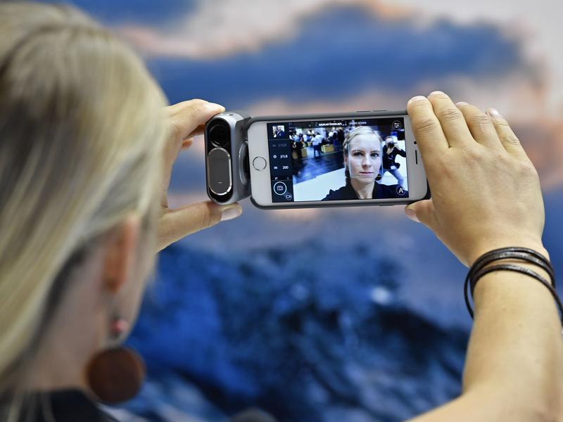"A woman takes a selfie with a DXO camera connected to an iPhone.  On its website, Photokina invites pros, traders, hobby photographers and young ""smartphoners"" to experience their dream products.  (Martin Meissner / AP)"