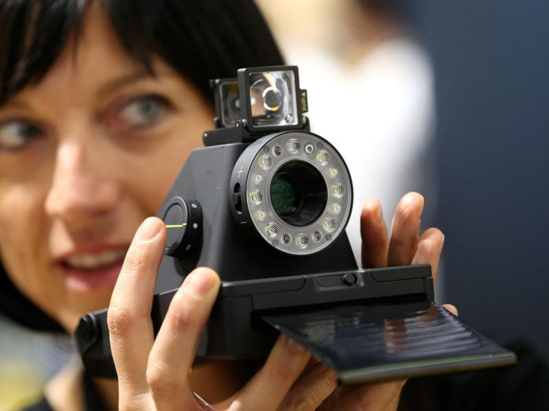 A woman takes a picture with the Impossible I-1 analog instant camera, the first new camera system working with the original Polaroid photo format.   (Fabrizio Bensch / REUTERS)