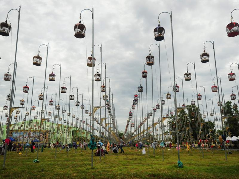 When they're ready to sing, the cages are lifted onto hooks and raised high into the air. Birds sit in their cages, hoisted on poles during a bird-singing contest. (AFP)