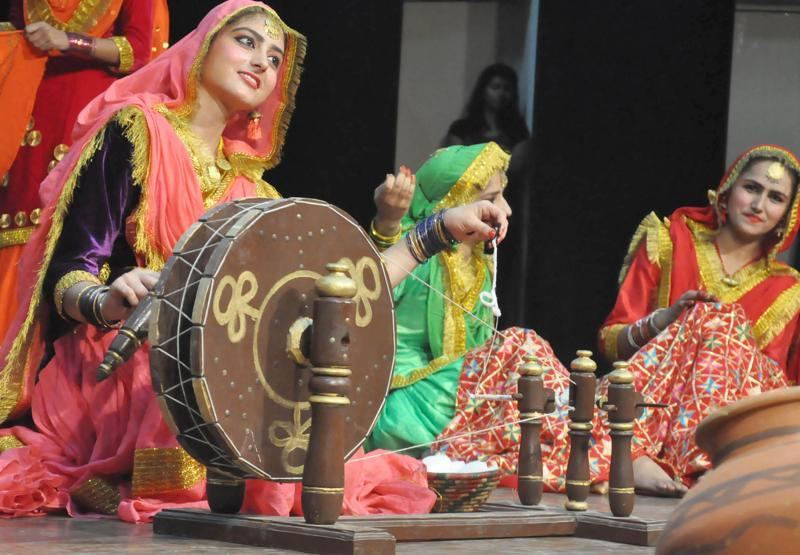 Students display the charkha during a giddha performance at Guru Nanak Dev University in Amritsar on Thursday. (HT Photo)