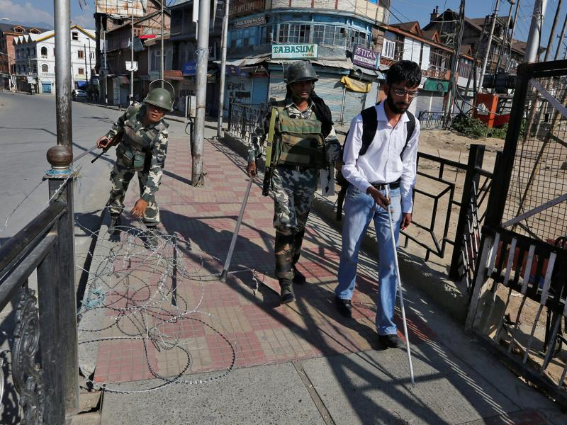 A policeman steers a visually impaired man clear of concertina wire laid on a pavement during curfew in Srinagar. (Danish Ismail/REUTERS)