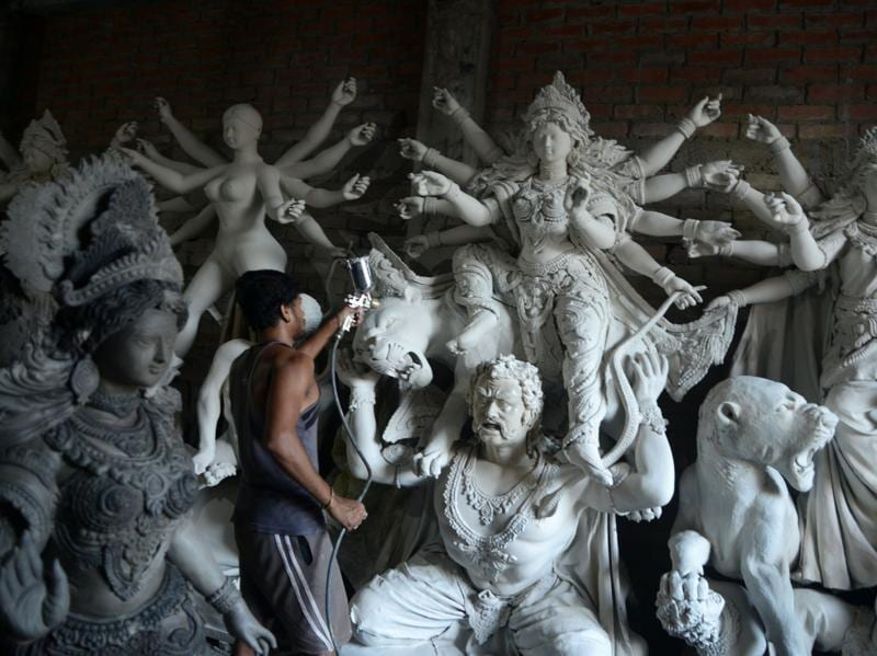 An artisan works on semi-finished clay idols of goddess Durga inside his workshop in Kumartoli, the idol makers' village of Siliguri, on September 22, 2016 The five-day period of worship of Durga, who is attributed as the destroyer of evil, commences on October 7.  (DIPTENDU DUTTA/AFP)