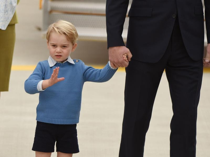 Her elder brother, Prince George wore his staple, shirt-sweater-shorts combo with knee-high sokcs. (AFP)