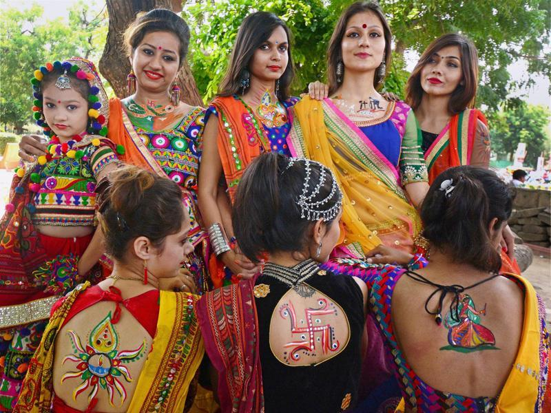 Colourful clothes and oxidised silver jewellery is so predictable. Girls are going the extra mile this year to show their enthusiasm. Notice the many tattoos.  (PTI)