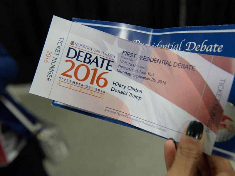 A woman holds a Presidential debate ticket with the name