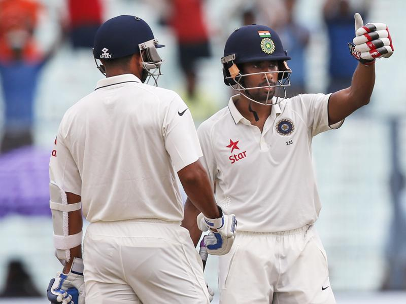 Wriddhiman Saha, right, gestures towards the dressing room after completing his half-century. (AP photo)