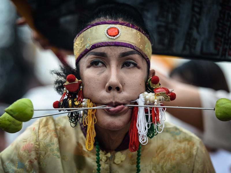 A devotee of the Nine Emperor Gods walks with needles through her face during the annual Phuket Vegetarian Festival in the southern province of Phuket, Thailand. Swords, axe handles, kebab skewers and even a model boat were just some of the objects placed in devotees' pierced cheeks as southern Thailand's vegetarian festival got under way.  (AFP Photo)