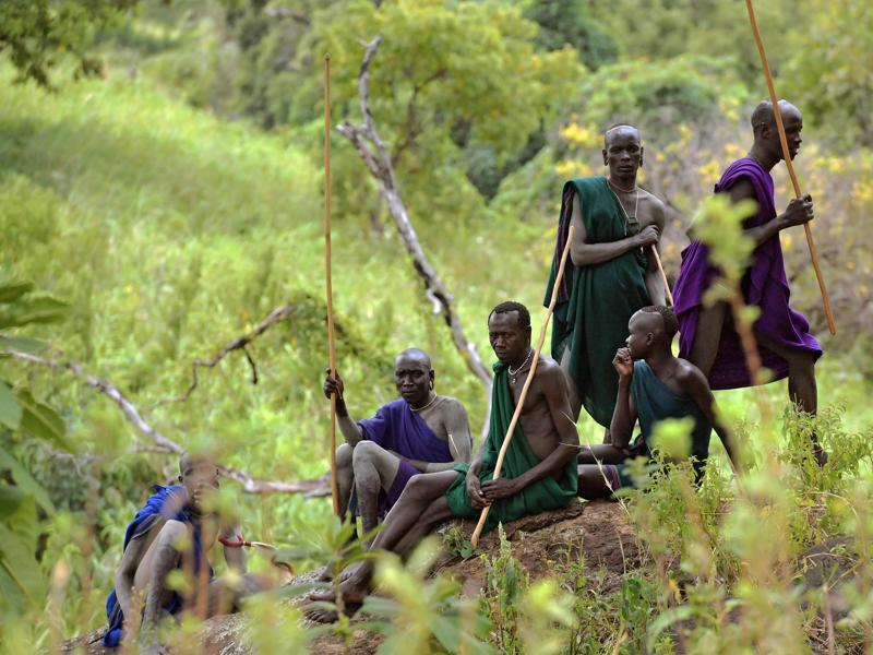 Men from the Suri tribe wait for a Donga or stick fight near Kibbish on September 24, 2016. Traditionally the fight is a way to impress women and find a wife. The fights are brutal and sometimes result in death. The combatants fight with little or no clothing and sometimes no protection at all.  (AFP)