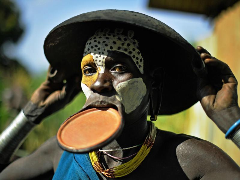 A woman from the Suri tribe with a lip plate poses for the camera on September 25, 2016.   (AFP)