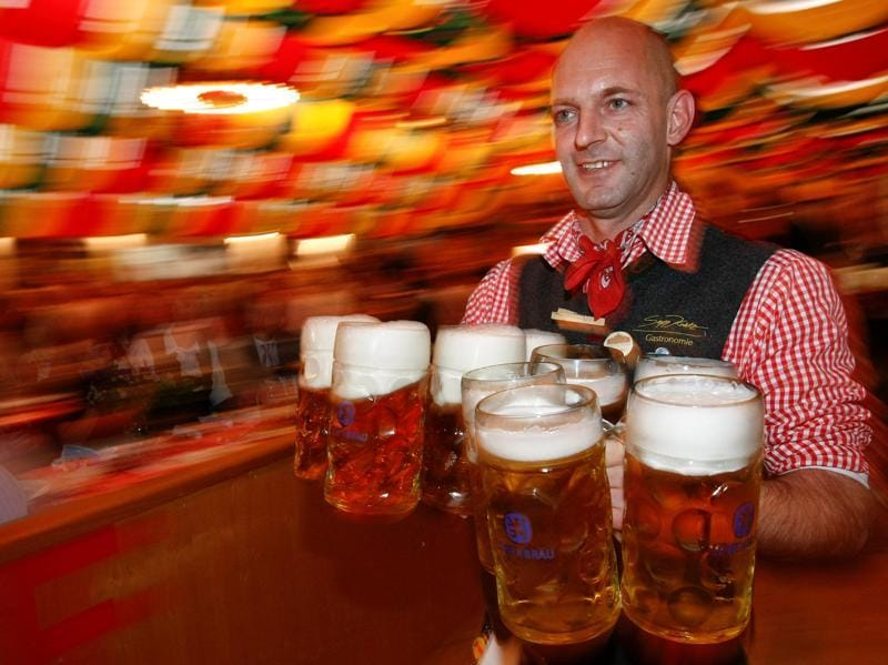A waiter serves mugs of beer during the opening of the Oktoberfest in Berlin. (REUTERS)